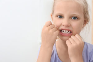 girl flossing teeth for complete dental care